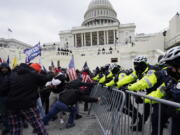 FILE - In this Jan. 6, 2021 file photo, Trump supporters try to break through a police barrier at the Capitol in Washington. With riot cases flooding into Washington's federal court, the Justice Department is under pressure to quickly resolve the least serious cases.