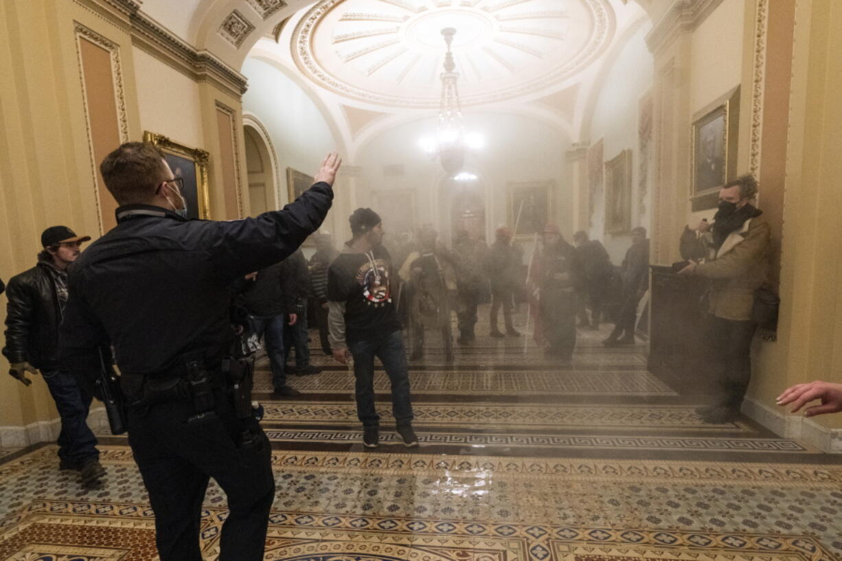 FILE - In this Jan. 6, 2021, file photo, smoke fills the walkway outside the Senate Chamber as supporters of President Donald Trump are confronted by U.S. Capitol Police officers inside the Capitol in Washington. With riot cases flooding into Washington's federal court, the Justice Department is under pressure to quickly resolve the least serious cases.