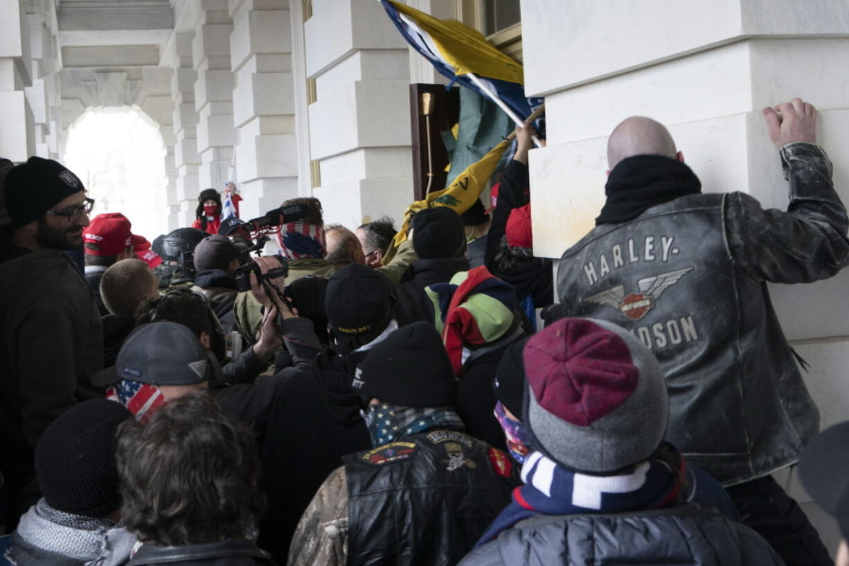 FILE - In this Jan. 6, 2021 file photo insurrectionists loyal to President Donald Trump try to open a door of the U.S. Capitol as they riot in Washington. At least a dozen of the 400 people charged so far in the Jan. 6 insurrection have made dubious claims about their encounters with officers at the Capitol. The most frequent argument is that they can't be guilty of anything, because police stood by and welcomed them inside, even though the mob pushed past police barriers, sprayed chemical irritants and smashed windows as chaos enveloped the government complex.