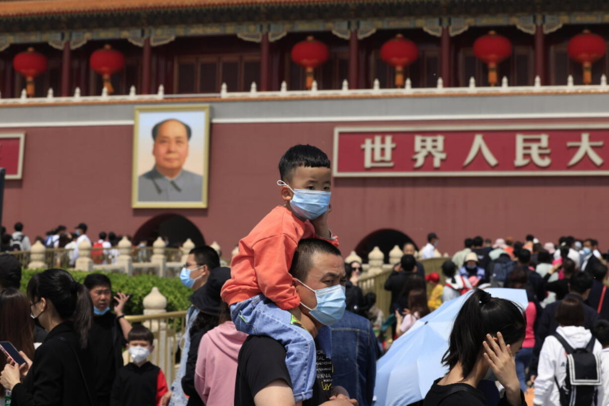A man and child wearing masks visit Tiananmen Gate near the portrait of Mao Zedong in Beijing on May 3, 2021. China's population growth is falling closer to zero as fewer couples have children, the government announced Tuesday, May 11, 2021, adding to strains on an aging society with a shrinking workforce.