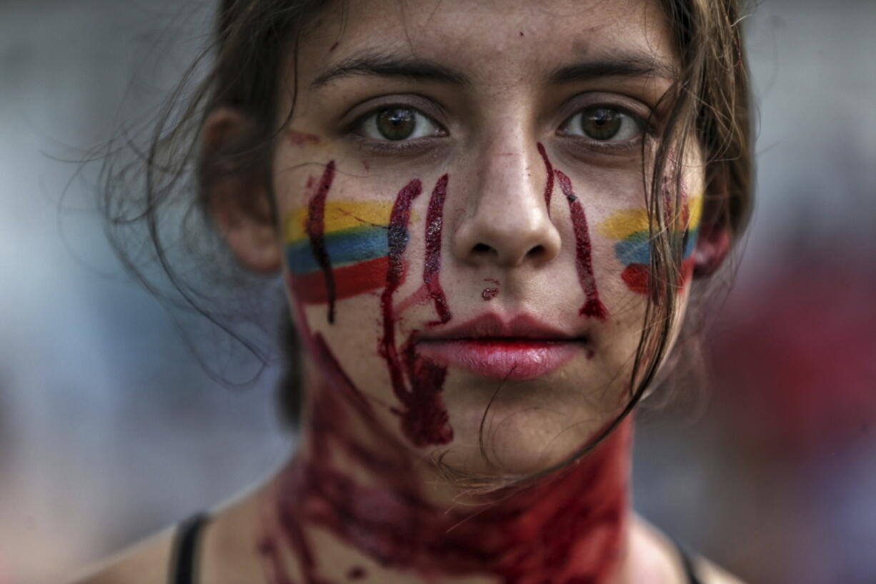 """A student performs a play called """"Who killed them"""" during anti-government protests in Cali, Colombia, Tuesday, May 11, 2021. Colombians have protested across the country against a government they feel has long ignored their needs, allowed corruption to run rampant and is so out of touch that it proposed tax increases during the coronavirus pandemic."""