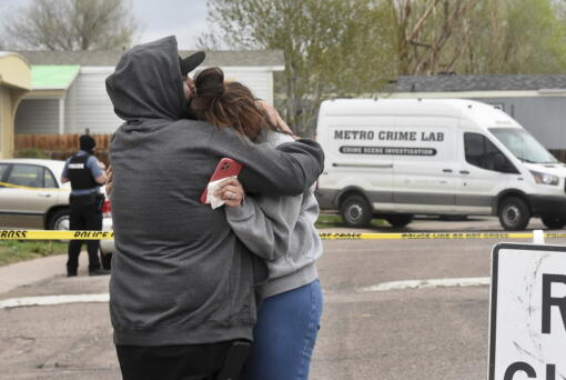 Freddy Marquez kisses the head of his wife, Nubia Marquez, near the scene where her mother and other family members were killed in a mass shooting early Sunday, May 9, 2021, in Colorado Springs, Colo.  The suspected shooter was the boyfriend of a female victim at the party attended by friends, family and children. He walked inside and opened fire before shooting himself, police said. Children at the attack weren't hurt and were placed with relatives.