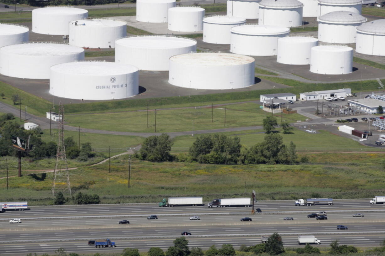 FILE - In this Sept. 8, 2008 file photo traffic on I-95 passes oil storage tanks owned by the Colonial Pipeline Company in Linden, N.J. A major pipeline that transports fuels along the East Coast says it had to stop operations because it was the victim of a cyberattack.