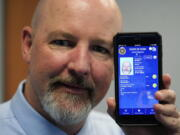 Ryan Williams, with the Utah Drivers License Division, displayes his cell phone with the pilot version of the state's mobile ID on Wednesday, May 5, 2021, in West Valley City, Utah. The card that millions of people use to prove their identity to everyone from police officers to liquor store owners may soon be a thing of the past as a growing number of states develop digital driver's licenses. In Utah, over 100 people have a pilot version of the state's mobile ID, and that number is expected to grow to 10,000 by year's end. Widespread production is expected to begin at the start of 2022.