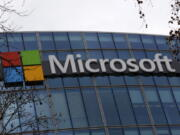 FILE - This Jan. 8, 2021 file photo shows the logo of Microsoft displayed outside the headquarters in Paris. Microsoft's business beat Wall Street expectations for the first three months of 2021, thanks to ongoing demand for its software and cloud computing services during the pandemic. The company on Tuesday, April 27, 2021 reported fiscal third-quarter profit of $14.8 billion, up 38% from the same period last year.