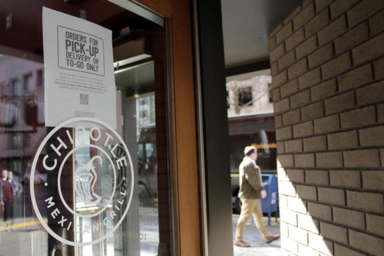 FILE - In this March 16, 2020, file photo, a sign indicating that only carry-out or delivery options are available hangs in the window of a closed Chipotle restaurant in Portland, Ore. U.S. restaurants and stores are rapidly raising pay in an urgent effort to attract more applicants and keep up with a flood of customers as the pandemic eases. McDonald's, Sheetz and Chipotle are just some of the latest companies to follow Amazon, Walmart and Costco in boosting wages, in some cases to $15 an hour or higher.