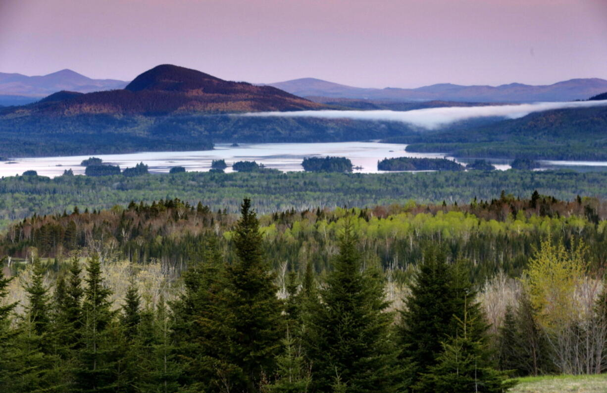 FILE - In this Tuesday, May 28, 2019, file photo is a view of Attean Pond near Jackman, Maine. Central Maine Power's controversial hydropower transmission corridor would be in the vicinity of this view from a scenic pullover. A 150-foot-wide swath of land would extend 53 miles from the Canadian border into Maine's north woods. (AP Photo/Robert F.