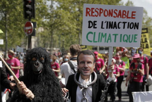 A protester wearing a mask depicting French President Emmanuel Macron holds a bord reading << Liable for climate inaction >> during a rally against the climate change in Paris, Sunday, May 9, 2021. Thousands of French demonstrators took to the streets of Paris and other cities on Sunday to call for more ambitious measures to fight against climate change.