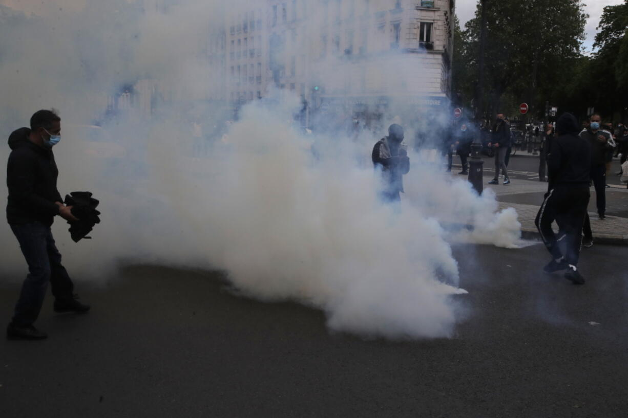 Demonstrators walk through tear gas grenades fired by police forces during a banned protest in support of Palestinians in the Gaza Strip, Saturday, May, 15, 2021 in Paris. Marches in support of Palestinians in the Gaza Strip were being held Saturday in a dozen French cities, but the focus was on Paris, where riot police got ready as organizers said they would defy a ban on the protest.