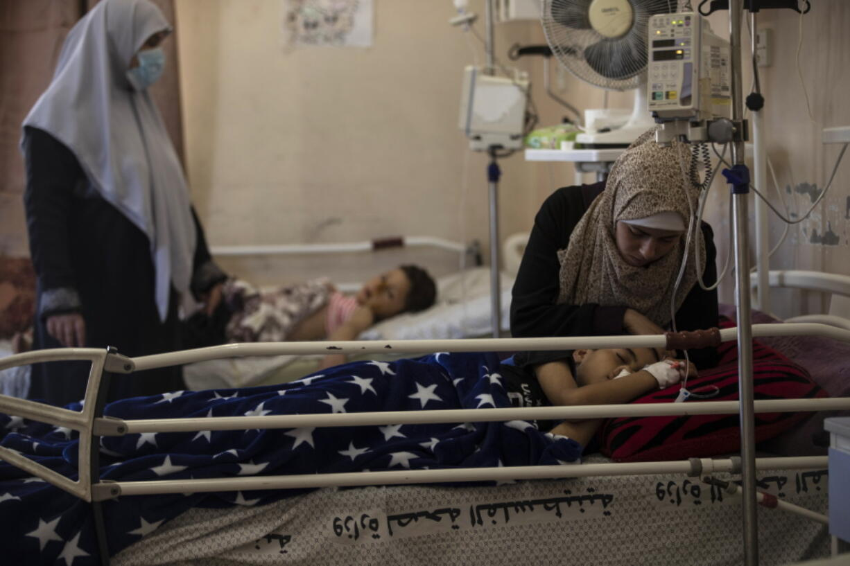 The mother of Yazan Al-zaharna, 9, comforts him as he rests at the Shifa hospital in Gaza City, Thursday, May 13, 2021, where he is receiving treatment for wounds caused by a May 10 Israeli strike that hit a nearby his family house in town of Jabaliya. Just weeks ago, the Gaza Strip's feeble health care system was struggling with a runaway surge of coronavirus cases. Now doctors across the crowded coastal enclave are trying to keep up with a very different crisis: blast and shrapnel wounds, cuts and amputations.