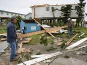 Mark Andollina, left, and Shane Holder clean debris left by Hurricane Zeta at the Cajun Tide Beach Resort in Grand Isle, La., on Oct. 30. The hurricane has been upgraded to a major, Category 3 storm.
