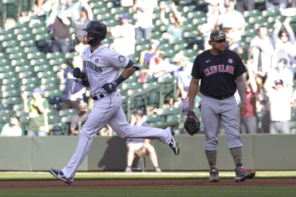 Seattle Mariners' Mitch Haniger runs past Cleveland Indians first baseman Josh Naylor following a solo home run during the first inning of a baseball game Saturday, May 15, 2021, in Seattle.