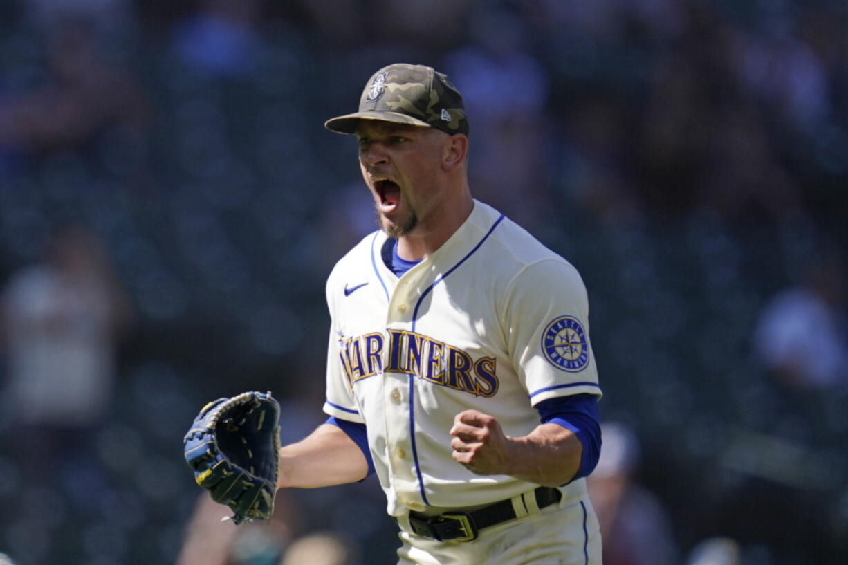 Seattle Mariners relief pitcher Anthony Misiewicz lets out a yell and pumps a fist after a double play with bases loaded ended the top of the seventh inning of a baseball game against the Cleveland Indians Sunday, May 16, 2021, in Seattle.