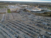 In this aerial photo, a General Motors assembly plant is seen at top right while mid-sized pickup trucks and full-size vans currently produced at the plant are seen in a parking lot outside Wednesday, March 24, 2021, in Wentzville, Mo.  U.S. industrial production increased for a second straight month as more factories came online after being shutdown by winter ice storms. Industrial production - which includes output at factories, mines and utilities - rose 0.7% in April, down from a sharp gain of 2.4% drop in March, the Federal Reserve reported Friday, May 14.