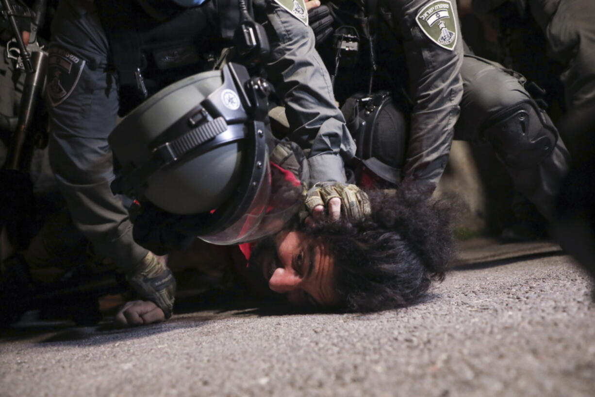 Israeli police officers detain a Palestinian demonstrator during a protest against the planned evictions of Palestinian families in the Sheikh Jarrah neighborhood of east Jerusalem, Tuesday, May 4, 2021.