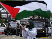 A demonstrator waves the flag of Palestine as police officers guard outside the Federal Building during a protest against Israel and in support of Palestinians, Saturday, May 15, 2021, in the Westwood section of Los Angeles. (AP Photo/Ringo H.W.