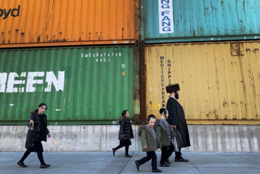Members of the Orthodox Jewish community walk past shipping containers in the South Williamsburg neighborhood of Brooklyn, New York, in March.