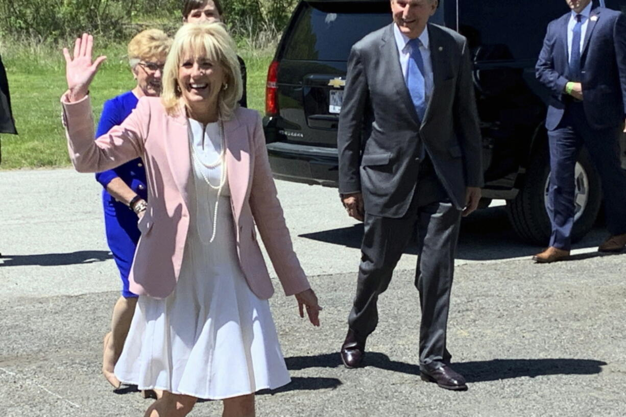 First lady Jill Biden arrives at a vaccination clinic Thursday, May 13, 2021, at a high school in Charleston, W.Va. Behind her are U.S. Sen. Joe Manchin of West Virginia and his wife, Gayle Manchin.
