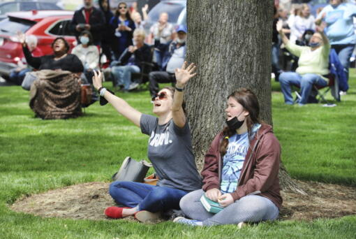 Rae Woodward, left, and Carrie Woodward sing along during a prayer worship service Thursday on the 70th National Day of Prayer on the lawn of the Daviess County Courthouse in Owensboro, Ky.