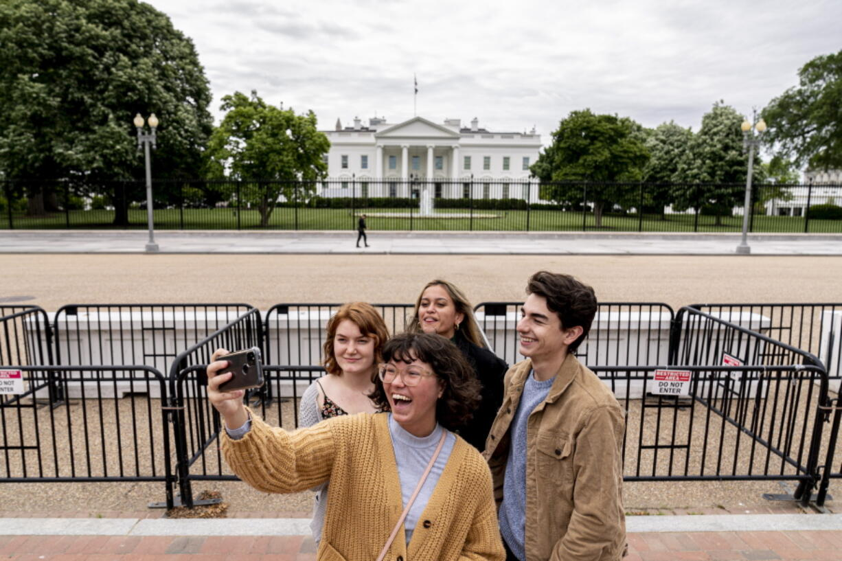 From left, Eliana Lord, Carly Mihovich, Stephanie Justice, and Nick Hansen, visiting from Columbia, S.C., take a photo at Lafayette Park, across the street from the White House, after it reopens in a limited capacity in Washington, Monday, May 10, 2021. Fencing remains in place around the park which will allow the Secret Service to temporarily close the park as they deem necessary.