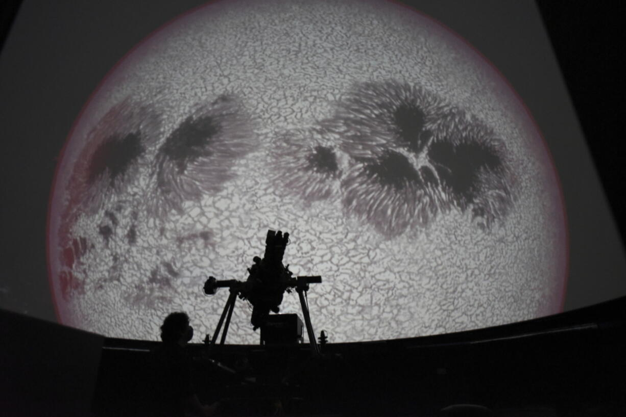 Researcher Ivannia Calvo, silhouetted against a solar satellite image, works inside the Solar Astronomical Observatory in San Jose, Costa Rica, Friday, April 30, 2021. Costa Rica approved a law creating a space agency on Feb. 18.