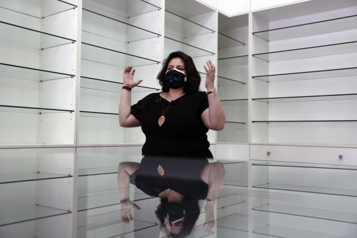 Pharmacist Rita El Khoury speaks in the middle of her empty pharmacy after selling her stock in preparation for her move to France with her husband, in Ballouneh, north of Beirut, Lebanon, Wednesday, April 21, 2021. They are part of the latest wave of emigration in the small country's tortured modern history, driven by financial ruin, collapsing institutions, hyperinflation and rapidly rising poverty.