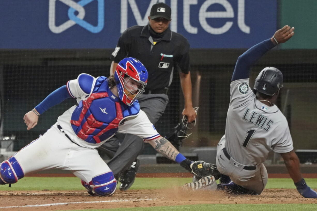 Seattle Mariners base runner Kyle Lewis is tagged out at home by Texas Rangers catcher Jonah Heim to end a baseball game in the ninth inning Saturday, May 8, 2021, in Arlington, Texas.