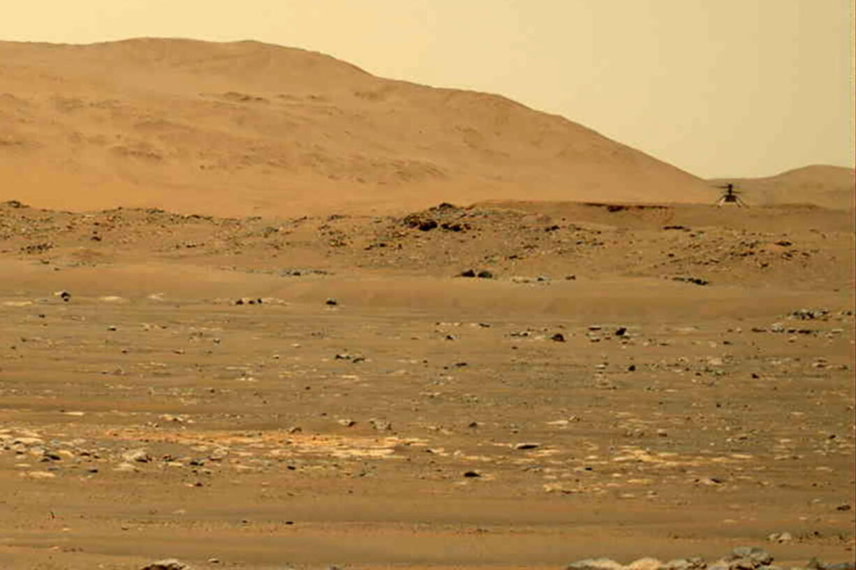 In this image taken by the Mars Perseverance rover and made available by NASA, the Mars Ingenuity helicopter, right, flies over the surface of the planet on Friday, April 30, 2021. Ingenuity made its fourth flight Friday afternoon, traveling 872 feet (266 meter) at a height of 16 feet (5 meters) for two minutes - considerably farther and longer than before.