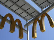 FILE- This Aug. 8, 2018, photo shows logos of McDonald's Chicago flagship restaurant. McDonald's is raising pay at 650 company-owned stores in the U.S. as part of its push to hire thousands of new workers in a tight labor market. The fast food giant is the latest restaurant chain to announce pay raises. (AP Photo/Nam Y.