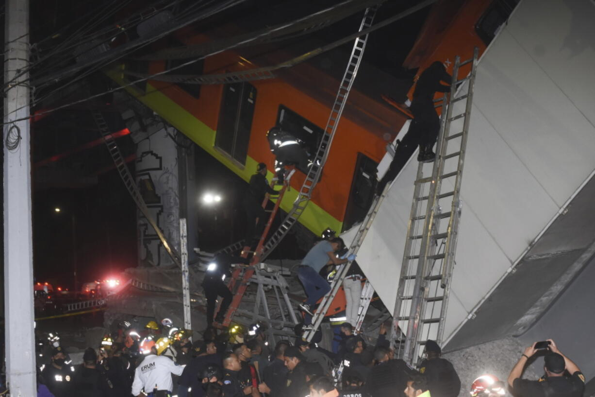 Mexico City fire fighters and rescue personnel work to recover victims from a subway accident after a section of Line 12 of the subway collapsed in Mexico City, Monday, May 3, 2021. The section passing over a road in southern Mexico City collapsed Monday night, dropping a subway train, trapping cars and causing at least 50 injuries and several dead, authorities said.