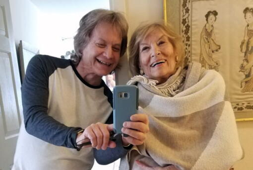 Leland Stein, left, takes a photo with his mother Sondra Green in her apartment in New York in  2018.