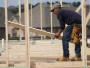 A carpenter aligns a beam for a wall frame at a new house site in Madison County, Miss., Tuesday, March 16, 2021.  U.S. home construction fell by a bigger-than-expected amount in April but the drop came after housing had risen to the highest level in 15 years. The Commerce Department said Tuesday, May 18, that construction dropped 9.5% in April to a seasonally adjusted annual rate of 1.57 million units.  % in April to an annual rate of 1.76 million units, a good sign that the April dip in construction will be temporary.  (AP Photo/Rogelio V.