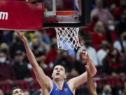 Denver Nuggets center Nikola Jokic, center, shoots over Portland Trail Blazers guard CJ McCollum, right, forward Robert Covington, second from right, and center Enes Kanter, left, during the first half of Game 3 of an NBA basketball first-round playoff series Thursday, May 27, 2021, in Portland, Ore.