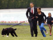 FILE - Int his April 14, 2009, file photo Malia Obama runs with Bo, followed by President Barack Obama and Sasha Obama, on the South Lawn of the White House in Washington. Former President Barack Obama's dog, Bo, died Saturday, May 8, 2021, after a battle with cancer, the Obamas said on social media.