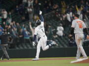 Seattle Mariners' Kyle Lewis celebrates after he hit a three-run home run as Baltimore Orioles first baseman Trey Mancini looks on during the eighth inning of a baseball game, Tuesday, May 4, 2021, in Seattle. (AP Photo/Ted S.