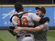 Baltimore Orioles starting pitcher John Means, right, hugs catcher Pedro Severino after Means threw a no-hitter in the team's baseball game against the Seattle Mariners, Wednesday, May 5, 2021, in Seattle. The Orioles won 6-0. (AP Photo/Ted S.