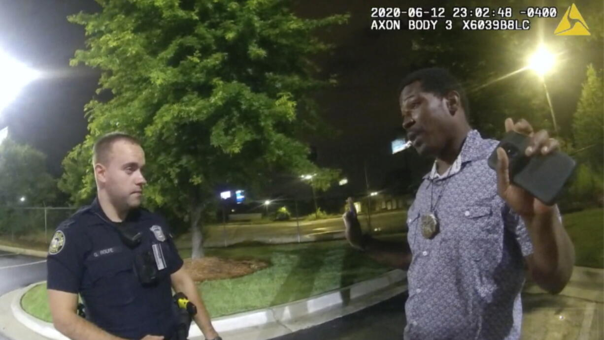 FILE - In this June 12, 2020, file photo from a screen grab taken from body camera video provided by the Atlanta Police Department Rayshard Brooks, right, speaks with Officer Garrett Rolfe, left, in the parking lot of a Wendy's restaurant, in Atlanta. Former Atlanta Police Officer, Rolfe's attorney said Thursday, April 22, 2021, that his client didn't get a chance to defend himself before he was fired for fatally shooting Brooks, a Black man who had been running away from two white officers after he resisted arrest and fired a stun gun at one of them.