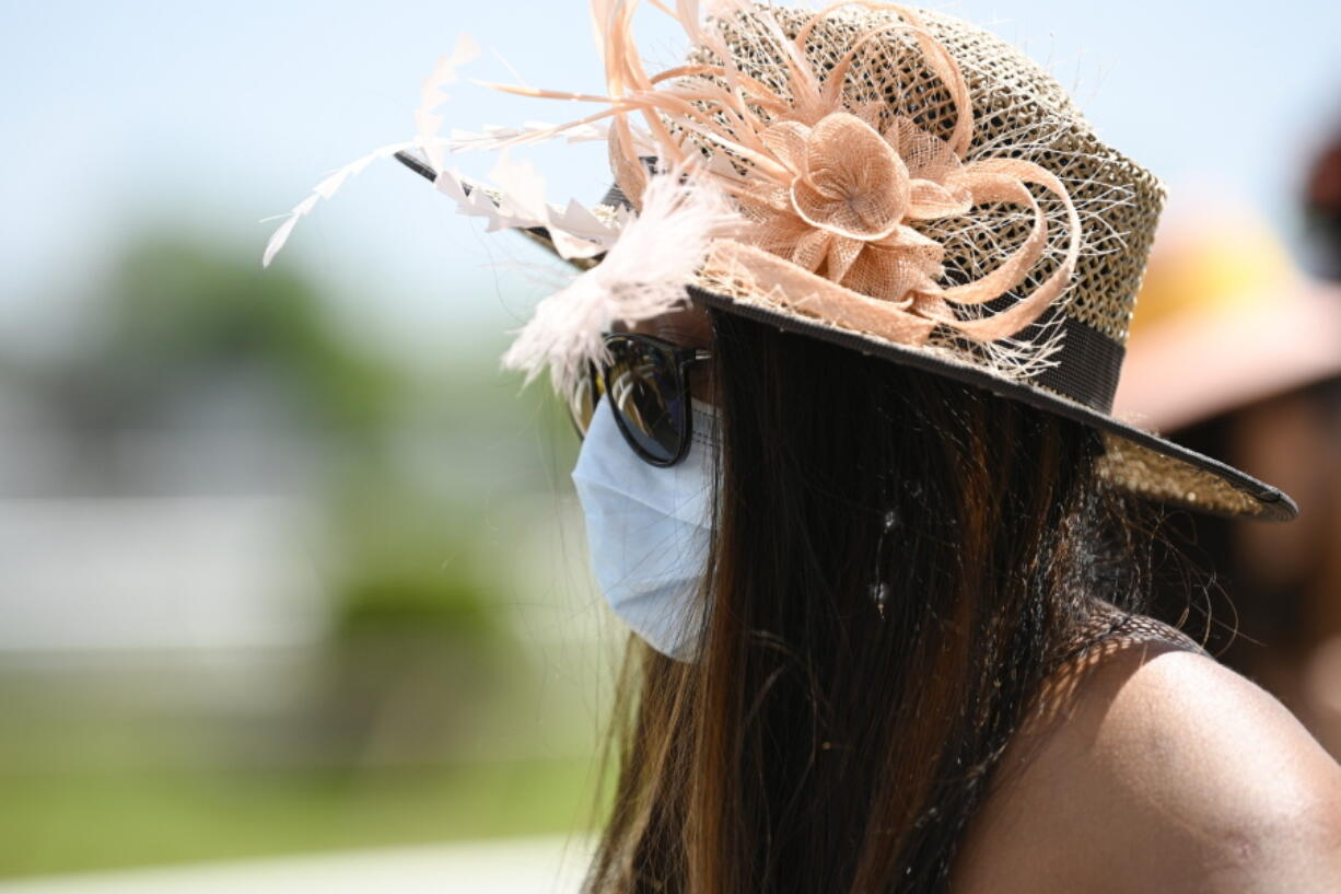 A woman wears a face mask to protect from the spread of COVID-19 ahead of the Preakness Stakes horse race at Pimlico Race Course, Saturday, May 15, 2021, in Baltimore.