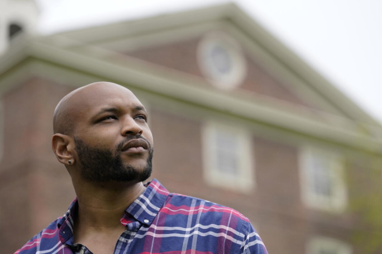 """Brown University graduate Jason Carroll, a Maryland native whose ancestors were slaves in the Carolinas, stands for a portrait on the Brown campus in Providence, R.I., on Tuesday, May 4, 2021, near University Hall, background, that was constructed in part using slave labor. """"There's real trauma and pain here,"""" says Carroll. """"This shouldn't just be an academic question."""