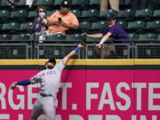 Texas Rangers right fielder Joey Gallo and a fan compete for the home run ball of Seattle Mariners' Kyle Seager in the fifth inning of a baseball game Sunday, May 30, 2021, in Seattle.