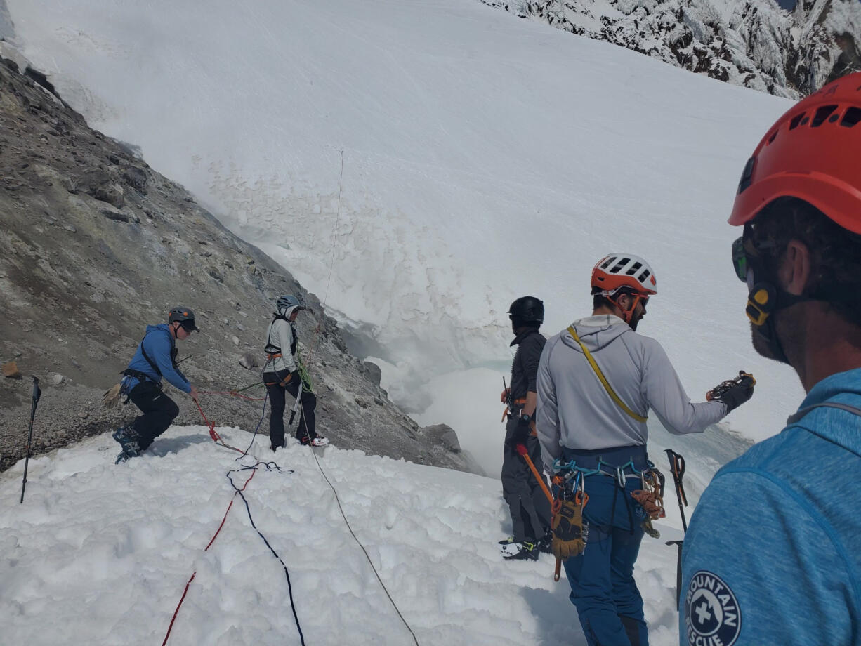 Rescue crews on Mount Hood begin descending a steep slope above where a climber fell to his death on Sunday morning.