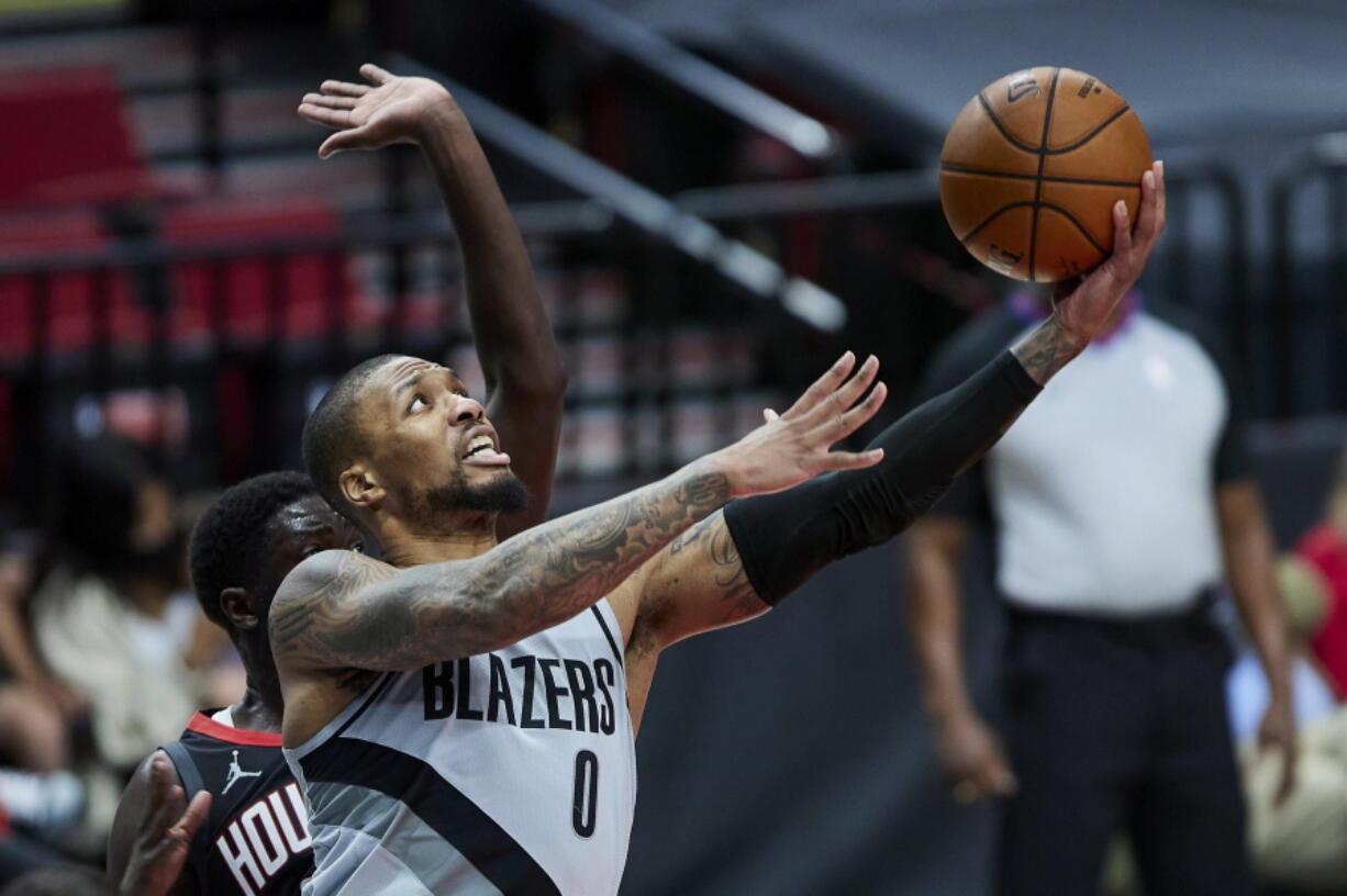 Portland Trail Blazers guard Damian Lillard (0) shoots in front of Houston Rockets forward Khyri Thomas during the second half on Monday in Portland.