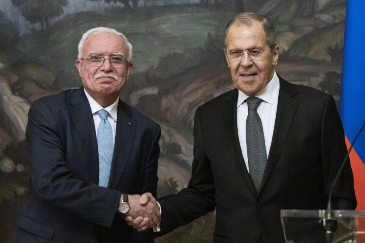 Russian Foreign Minister Sergey Lavrov, right, and Palestinian Foreign Minister Riyad Al-Maliki shake hands as they leave a joint news conference following their talks in Moscow, Russia, Wednesday, May 5, 2021.