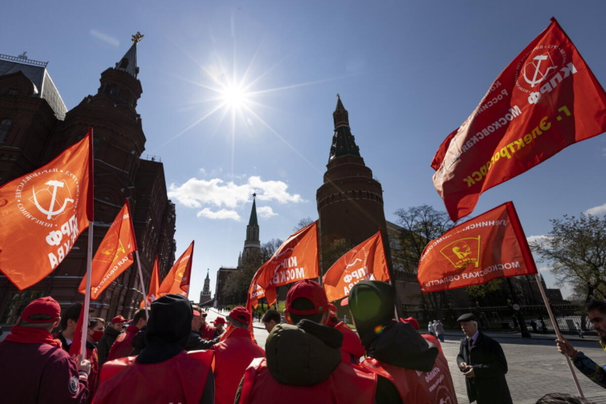 Communists party supporters gather with red flags to mark Labour Day, also knows as May Day near Red Square in Moscow, Russia, Saturday, May 1, 2021.