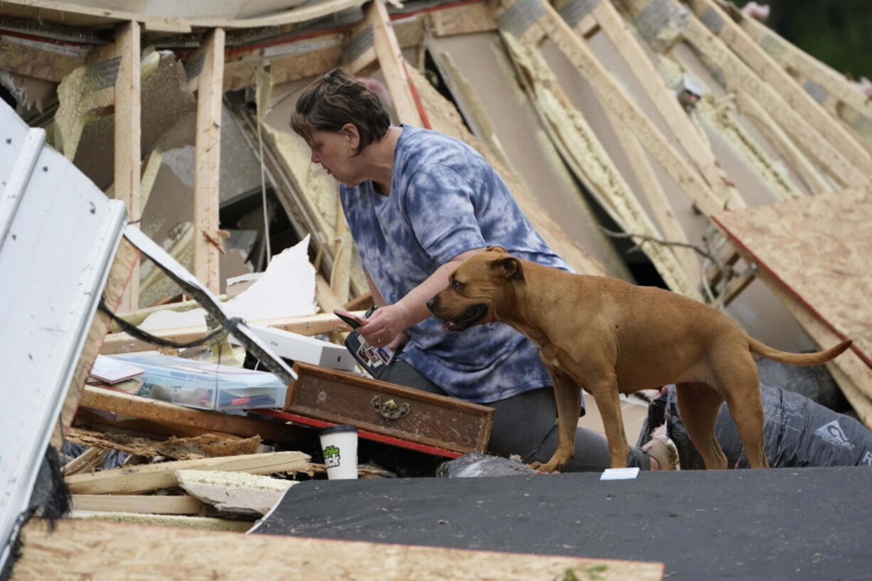 Vickie Savell looks through her belongings amid the remains of her new mobile home early Monday, May 3, 2021, in Yazoo County, Miss. Multiple tornadoes were reported across Mississippi on Sunday, causing some damage but no immediate word of injuries. (AP Photo/Rogelio V.