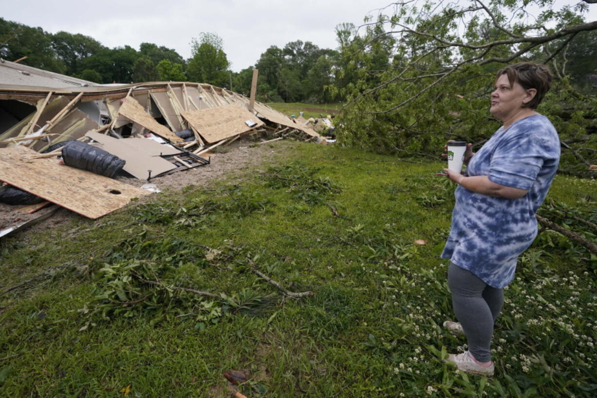 Vickie Savell looks at the remains of her new mobile home early Monday, May 3, 2021, in Yazoo County, Miss. Multiple tornadoes were reported across Mississippi on Sunday, causing some damage but no immediate word of injuries. (AP Photo/Rogelio V.