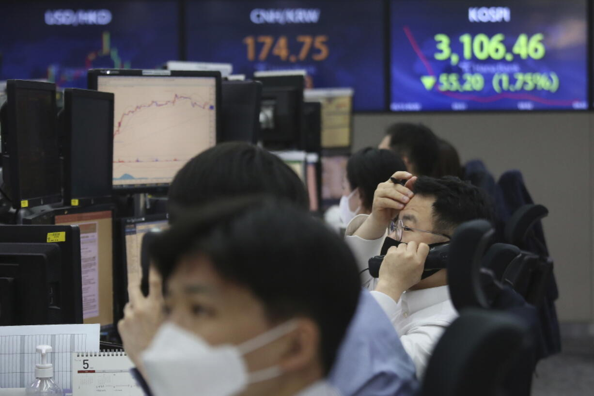 A currency trader talks on the phone at the foreign exchange dealing room of the KEB Hana Bank headquarters in Seoul, South Korea, Thursday, May 13, 2021. Asian stock markets followed Wall Street lower for a second day Thursday after unexpectedly strong U.S. consumer price rises fueled worries inflation might drag on an economic recovery.