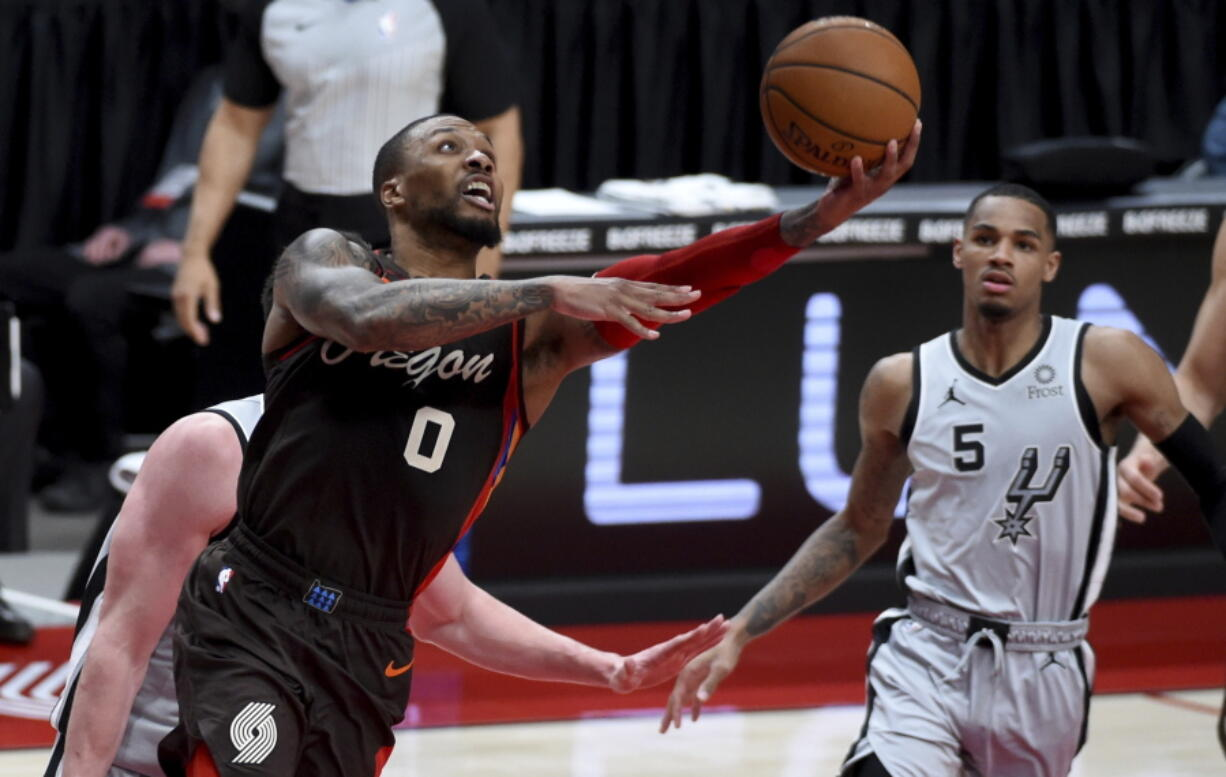 Portland Trail Blazers guard Damian Lillard, left, shoots as San Antonio Spurs guard Dejounte Murray, right, watches during the second half of an NBA basketball game in Portland, Ore., Saturday, May 8, 2021.