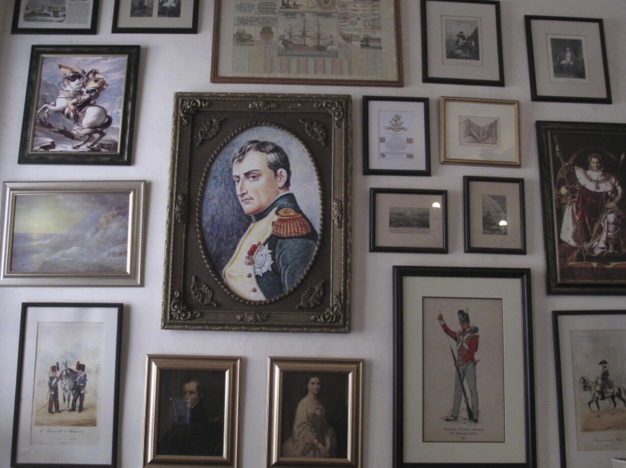 FILE - In this Oct. 15, 2017, file photo, several images of Napoleon Bonaparte are shown in this collection of framed pictures on a wall in the Consulate hotel in Jamestown on St. Helena island in the Atlantic Ocean. Commemorations of the May 5, 1821 death of Napoleon are going ahead on St. Helena, the remote South Atlantic island where the deposed French emperor died in exile. But they are not happening with an influx of international visitors that was expected before COVID-19 swept across the world. While the volcanic island has not had any confirmed COVID-19 cases, reaching it got even harder because of travel restrictions during the pandemic.