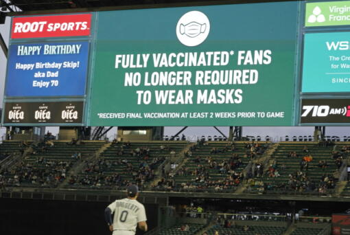 Fans sit in a special section for people who are fully vaccinated against COVID-19, at T-Mobile Park during a baseball game between the Seattle Mariners and the Detroit Tigers, Monday, May 17, 2021, in Seattle. Monday was the first day that fans fully vaccinated against COVID-19 were not required to wear masks at the ballpark, as shown on the video display. (AP Photo/Ted S.